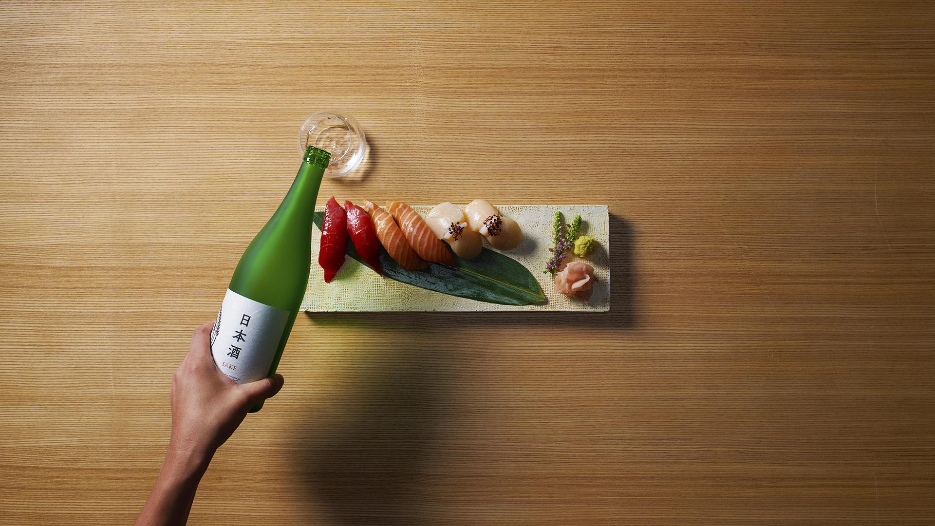 What is Sake?: Woman pouring bottle of sake for Japan Week